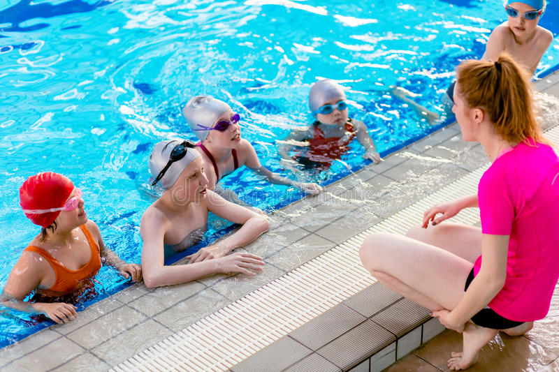 Happy children kids group at swimming pool class learning to swim royalty free stock images