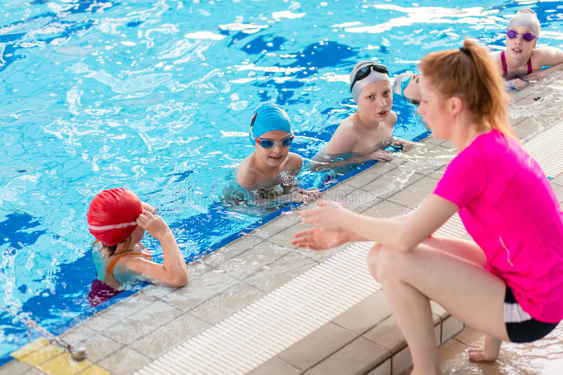 Happy children kids group at swimming pool class learning to swim royalty free stock photos