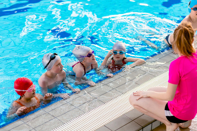 Happy children kids group at swimming pool class learning to swim stock images