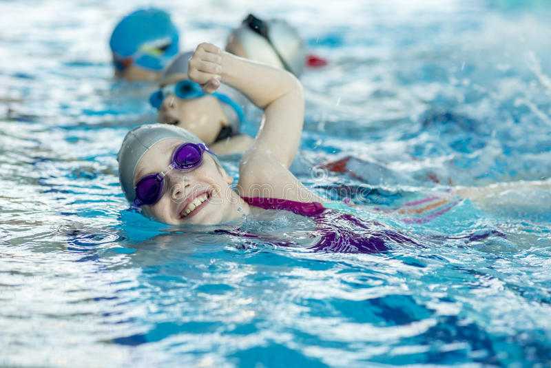 Happy children kids group at swimming pool class learning to swim.  stock photos