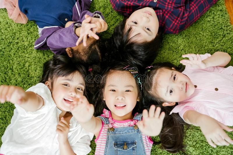 Happy children kids laying on grass green carpet floor in living room at home. stock photos