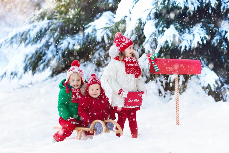 Children with letter to Santa at Christmas mail box in snow. Happy children in knitted reindeer hat and scarf holding letter to Santa with Christmas presents royalty free stock images