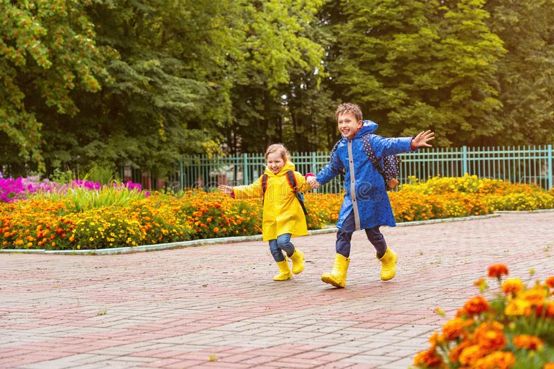 Happy children laugh, rush and run to school, dressed in raincoats, with a briefcase behind a backpack. Brother and sister in the rain in a hurry to get to stock photography
