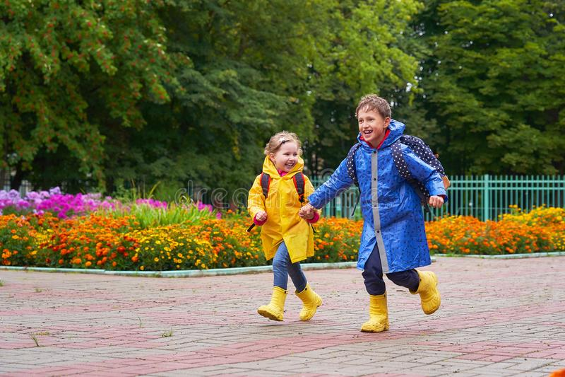 Happy children laugh, rush and run to school, dressed in raincoats, with a briefcase behind a backpack. Brother and sister in the rain in a hurry to get to stock image