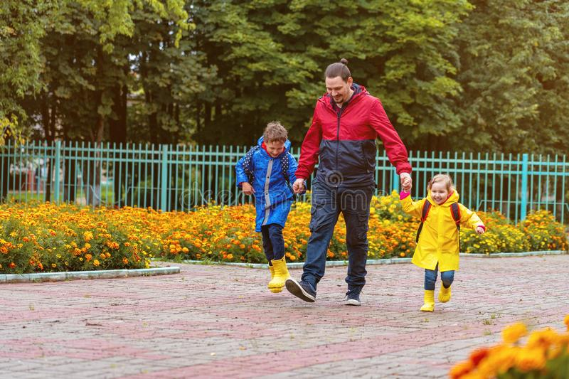 Happy children laugh, rush and run to school, dressed in raincoats, with a briefcase behind a backpack. Dad leads his daughter and son daroga to school in royalty free stock photo