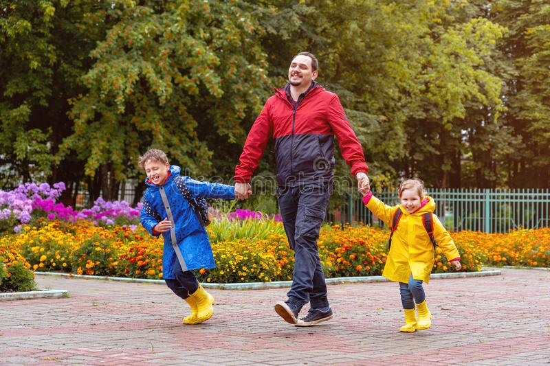 Happy children laugh, rush and run to school, dressed in raincoats, with a briefcase behind a backpack. Dad leads his daughter and son daroga to school in royalty free stock photos