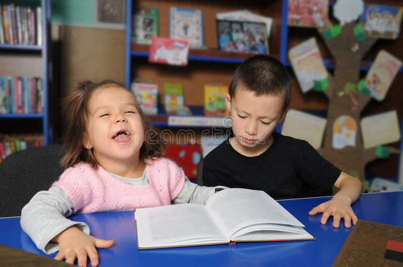 Happy children in library interesting reading book. Little girl and boy together learning stock photo
