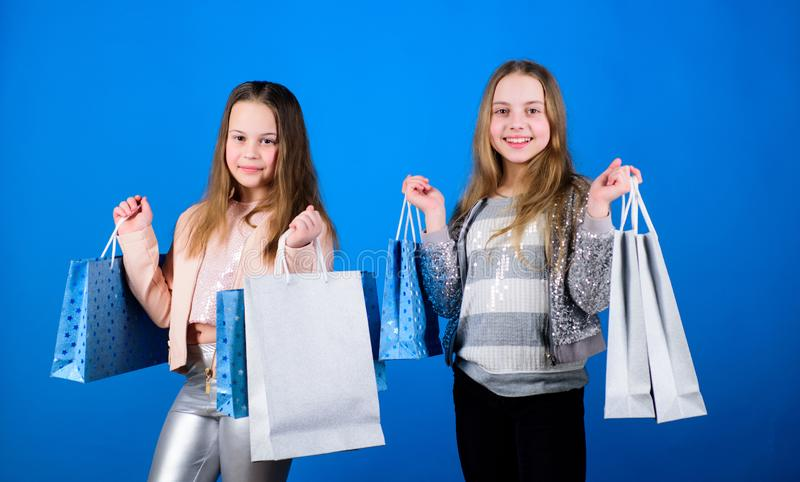 Happy children. Little girl sisters. Sales and discounts. Sisterhood and family. savings on purchases. Kid fashion. Blue. Background. Small girls with shopping royalty free stock images