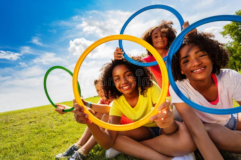 Happy children look through colorful hoops rings. Group of kids boy and girls sit in the park with colorful hoops showing happy smiles stock image