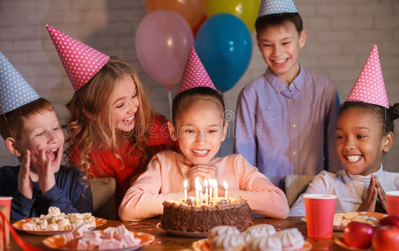 Happy children looking at birthday cake with candles. Having b-day party stock photo
