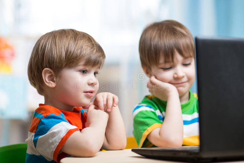 Happy children looking at laptop. Happy children boys looking at laptop indoors stock photography