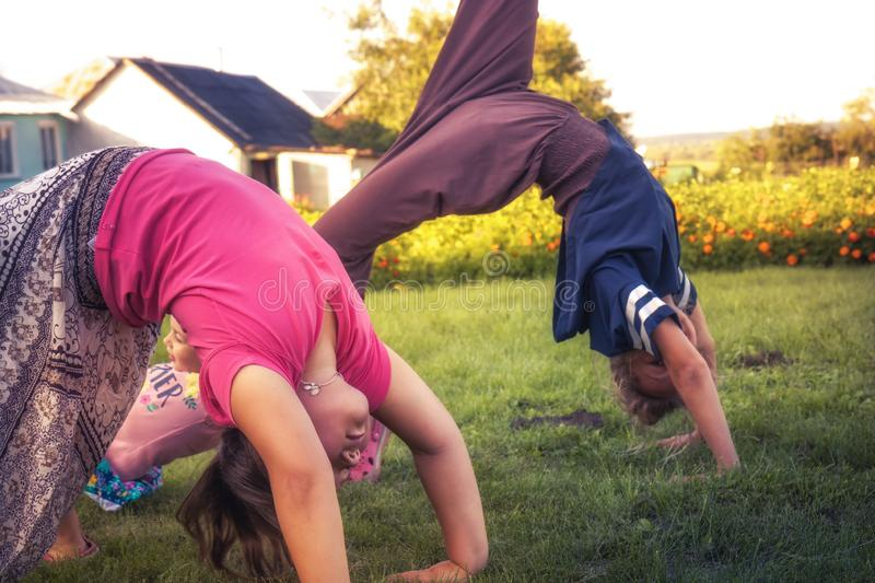 Happy children making exercise yoga outdoors on grass concept healthy childhood lifestyle stock images