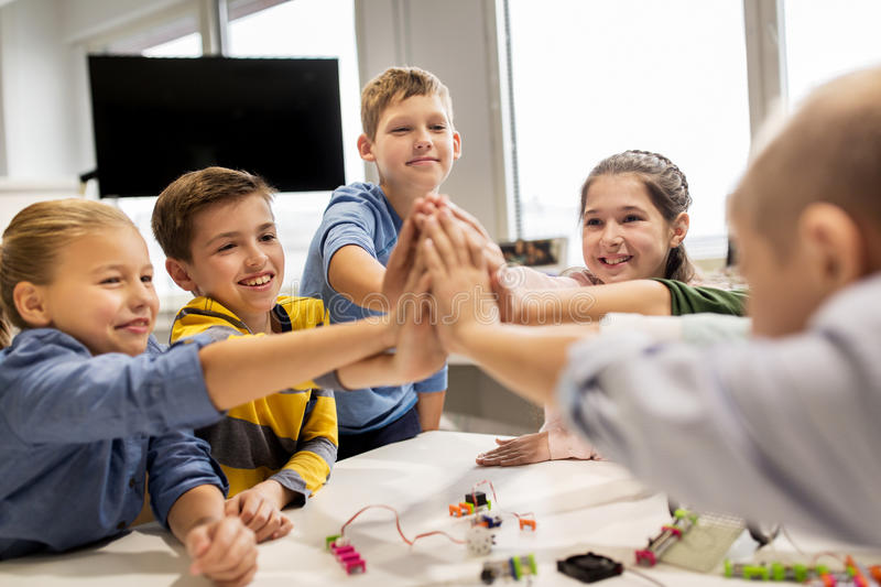 Happy children making high five at robotics school royalty free stock photography