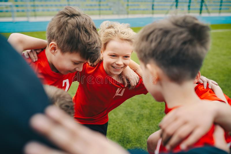 Happy children making sport. Group of happy boys making sports huddle. Smiling kids standing together with coach on grass sports field. Boys talking with coach royalty free stock photo