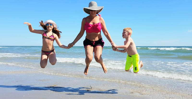 Happy children and mom jump on the beach in a sunny day of summer stock image