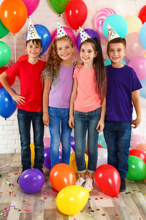 Happy children near balloons at birthday party royalty free stock photography