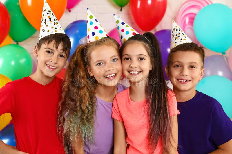 Happy children near bright balloons at birthday party royalty free stock photos