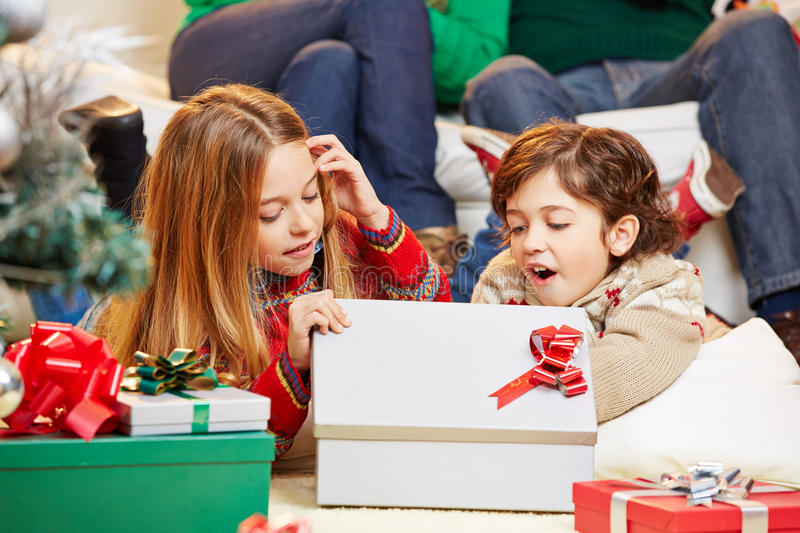 Happy children opening gifts together at christmas. Two happy children opening gifts together at christmas eve stock photo