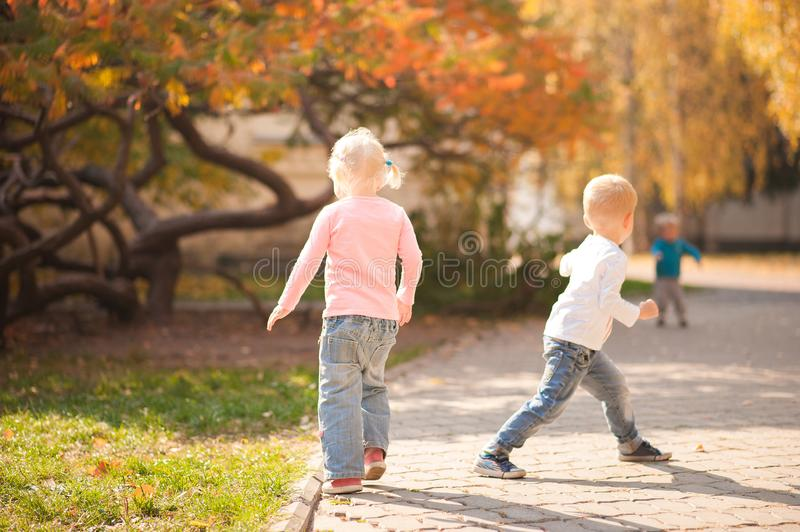 Happy children play in the park closeup. Boy and girl run and have fun in the autumn in the sun and copy space. Happy childhood mo stock photos