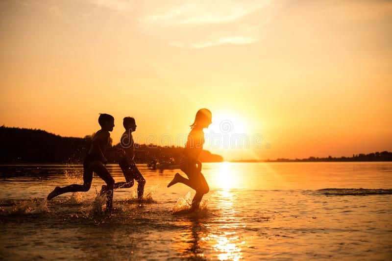 Happy children playing on the beach at the sunset time. Three Kids having fun outdoors. Concept of summer vacation and friendly family royalty free stock photo