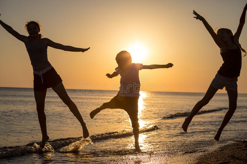 Happy children playing on the beach at the sunset time stock images