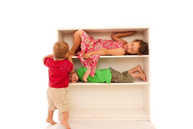 Happy children playing on fun kids bookshelf stock photos