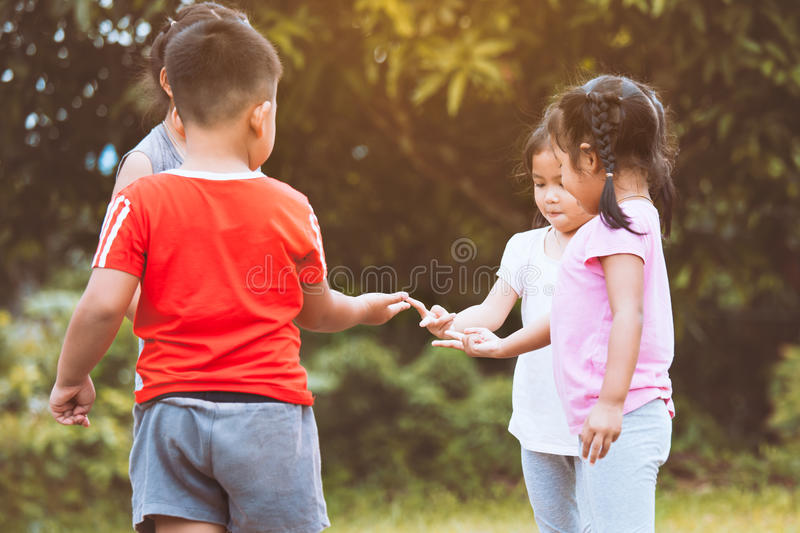 Happy children playing and having fun together in the park. In vintage color tone stock photography