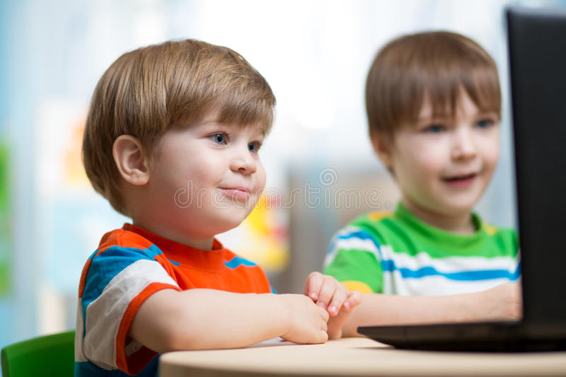 Happy children playing at laptop. Happy children boys playing at laptop at home royalty free stock images