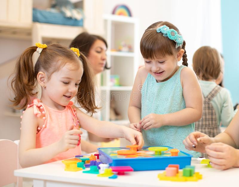 Happy kids playing with plastic building blocks at kindergarten royalty free stock images