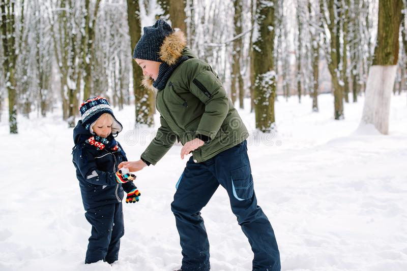 Happy children playing with snow in park. Happy family winter vacation. Brothers having fun together outdoors stock image