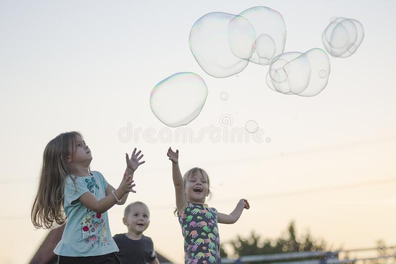 Happy children playing with soap bubbles. The happy children are playing with soap bubbles outdoors on sky background stock images