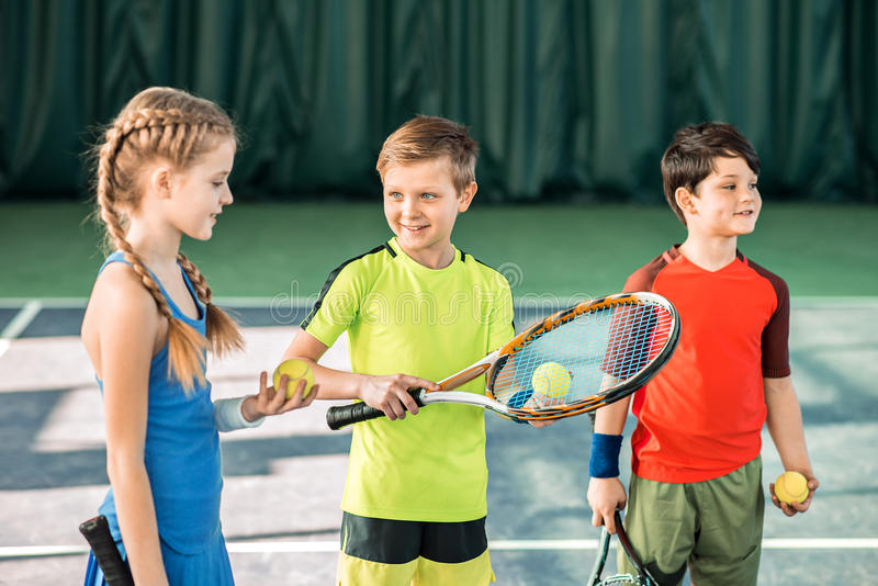 Happy children playing tennis on playground royalty free stock images