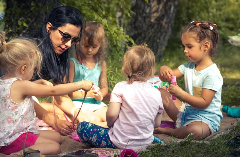 Happy children playing together with mother outdoors on grass lawn in park as big family lifestyle symbolizing happy childhood royalty free stock photos