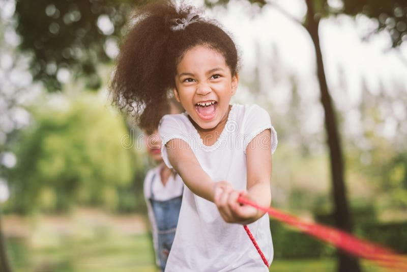 Happy children playing tug of war at the park. stock photo