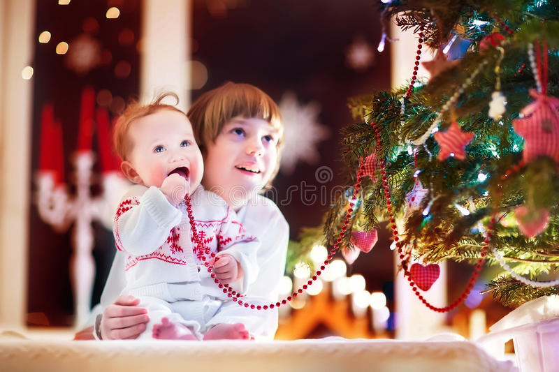 Happy children playing under a beautiful Christmas tree royalty free stock photography