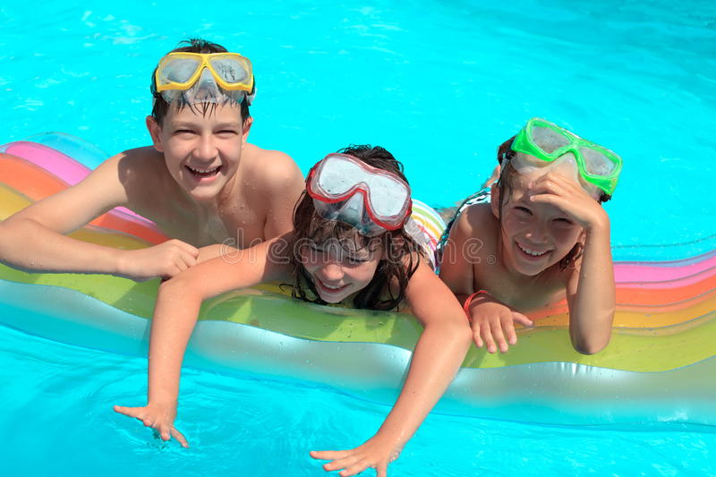 Happy children in pool. A group of happy children playing with an air mattress in a swimming pool stock image