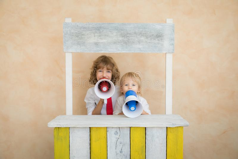Success, start up and business idea concept. Happy children pretend to be businessmen. Funny kids speaking at megaphone. Education, start up and business idea stock photo