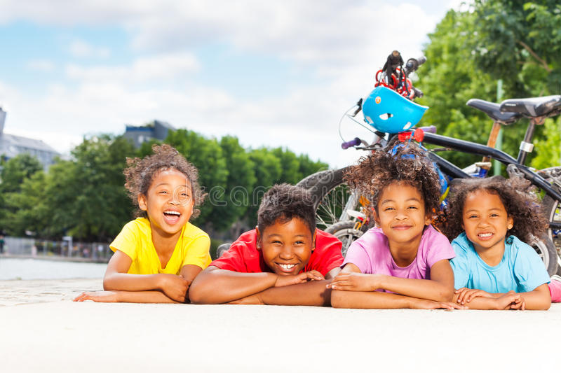 Happy children resting after cycling outdoors. Four happy age-diverse African children laying on the floor in line, resting after cycling at sunny day stock images