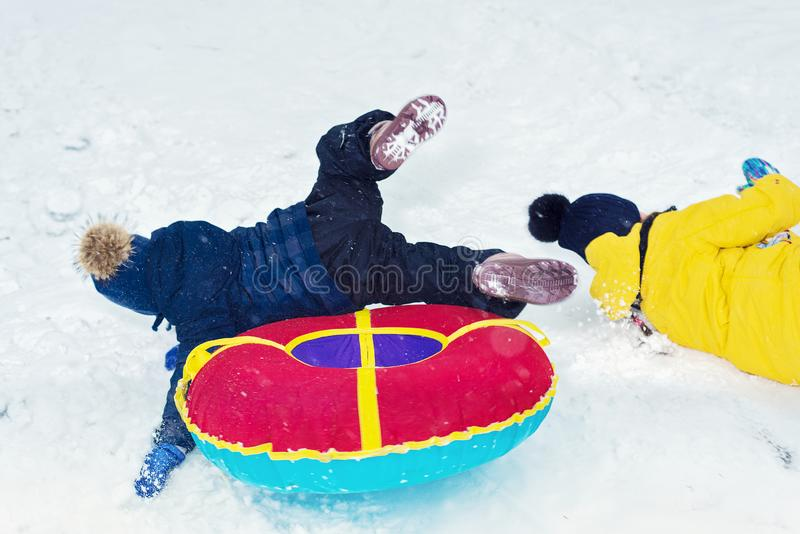 Happy children ride a winter slide on a sled. brother and sister play together royalty free stock photos