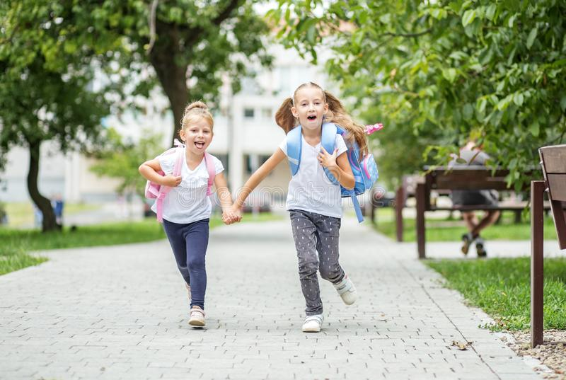Happy children run from school with backpacks. The concept of school, study, education, friendship, childhood. Happy children run from school with backpacks royalty free stock photos