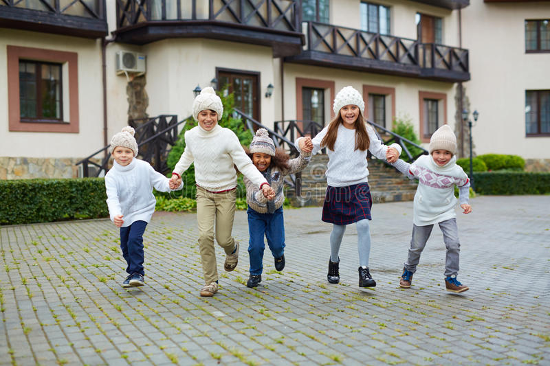 Happy Children Running outdoors in Autumn. Group of happy children playing outdoors and running towards camera holding hands, all wearing similar knit clothes on royalty free stock photo