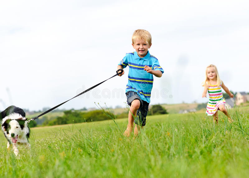 Happy children running outdoors with dog stock photos