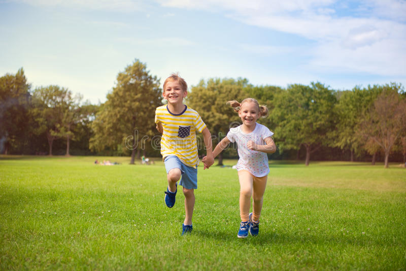 Happy children running in park stock photography