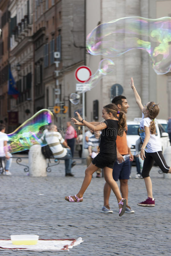 Happy children running towards a soap bubble stock photography