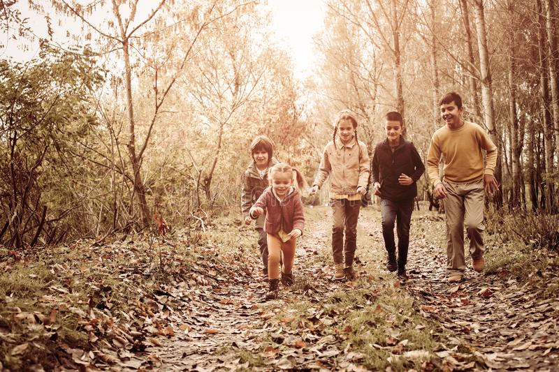 Happy children running trough the park together. royalty free stock photo