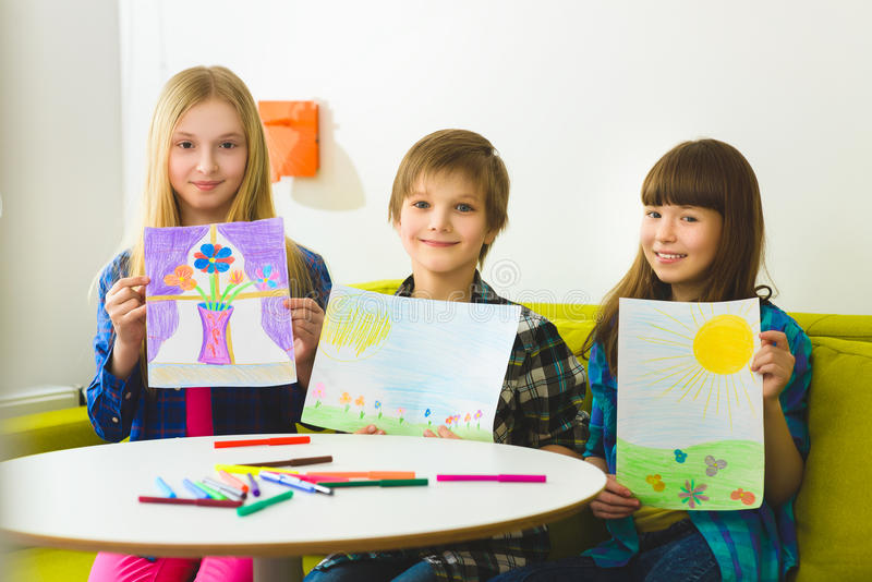 Happy children show their pictures drawn. Indoor at room.  royalty free stock images