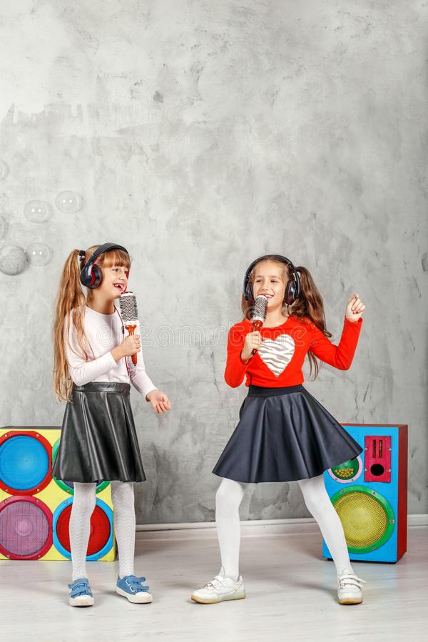 Happy children sing and listen to music in headphones. The conce. Pt is childhood, lifestyle, dance, music royalty free stock image