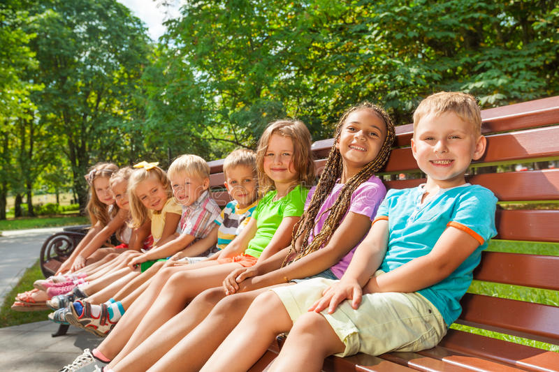 Happy children sit on the bench in park royalty free stock photo