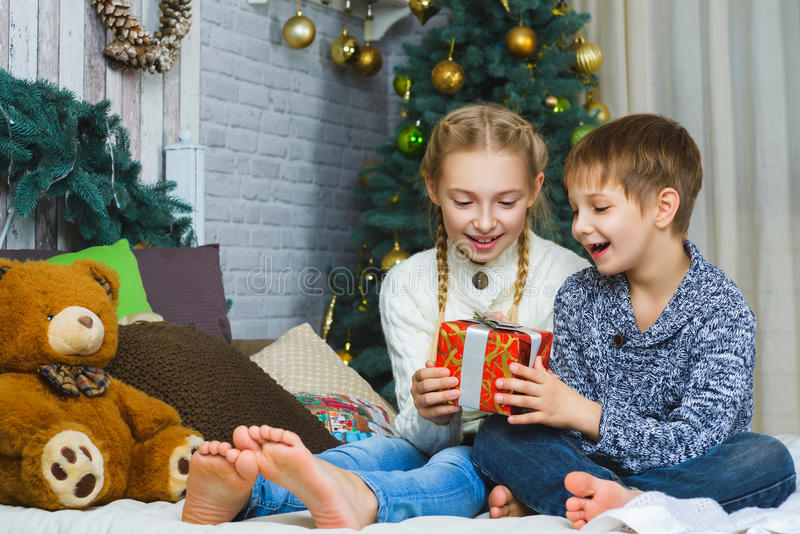 Download Happy Children Sitting On Bed And Holding Gifts Stock Photo    Image Of Girl,