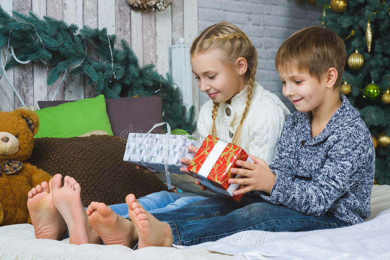Happy children sitting on bed and holding gifts royalty free stock photo